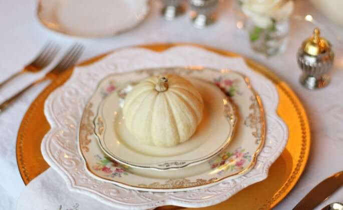 A Thanksgiving place setting, including ornate plates, a gold charger, and a decorative pumpkin.