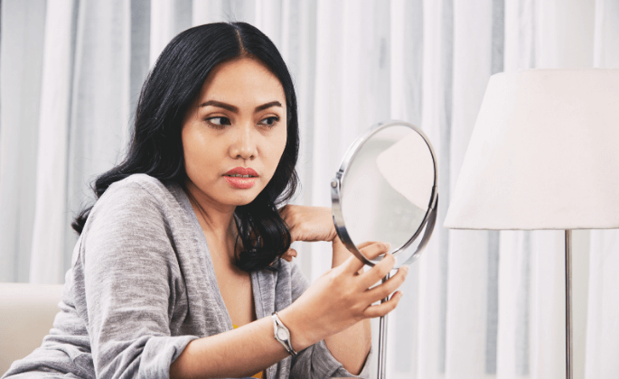 A person checks appearance in the mirror