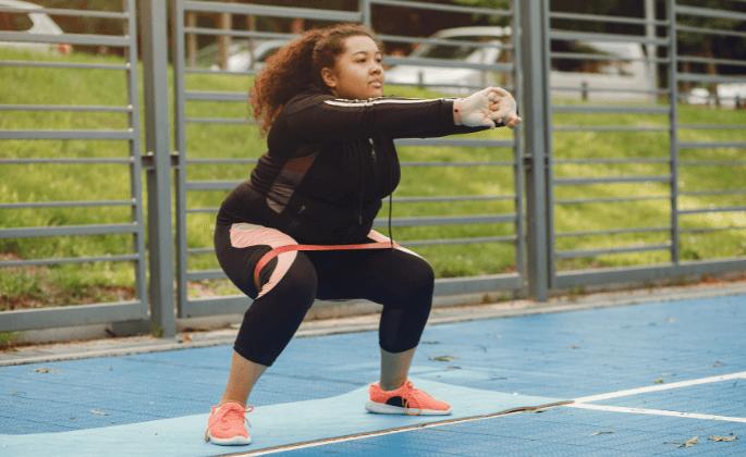 A woman exercising outside on a yoga mat
