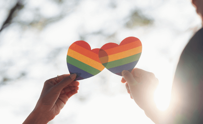 Two rainbow hearts held together by two hands