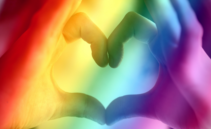 A heart made from hands set with a rainbow filter