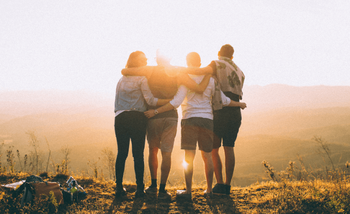 A group of friends standing on cliff during a sunset