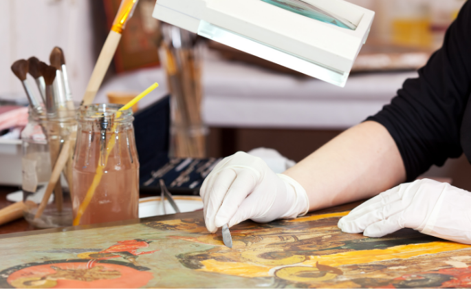 A close-up view of a painting under restoration