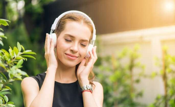 Woman listening to headphones in the sun