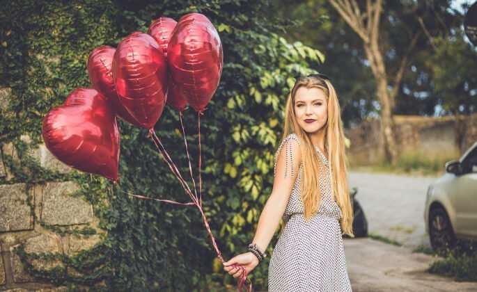 Woman holding heart balloons