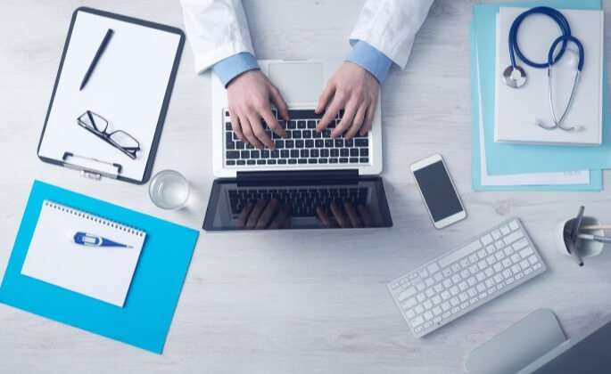 A doctor's desk with a laptop, notebooks, and stethoscope