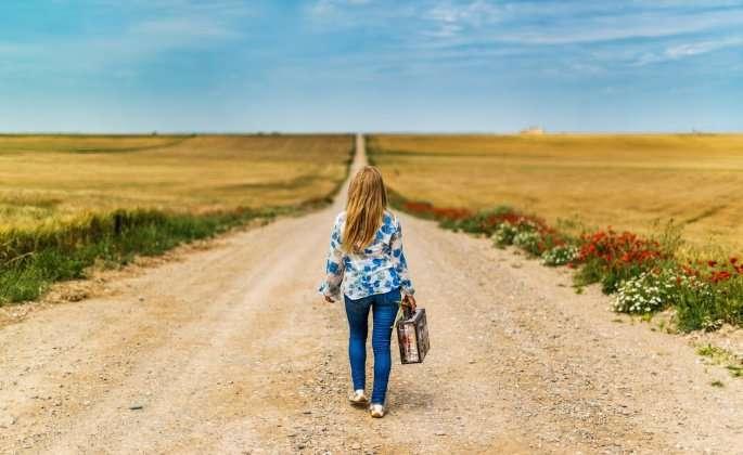 Woman walking along empty gravel road
