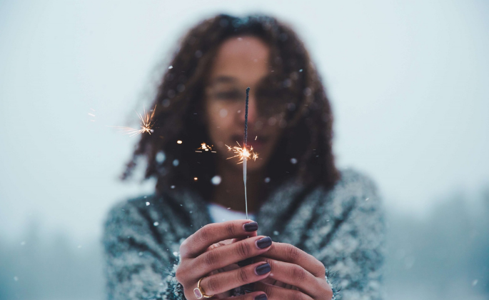 A person holding a sparkler outside