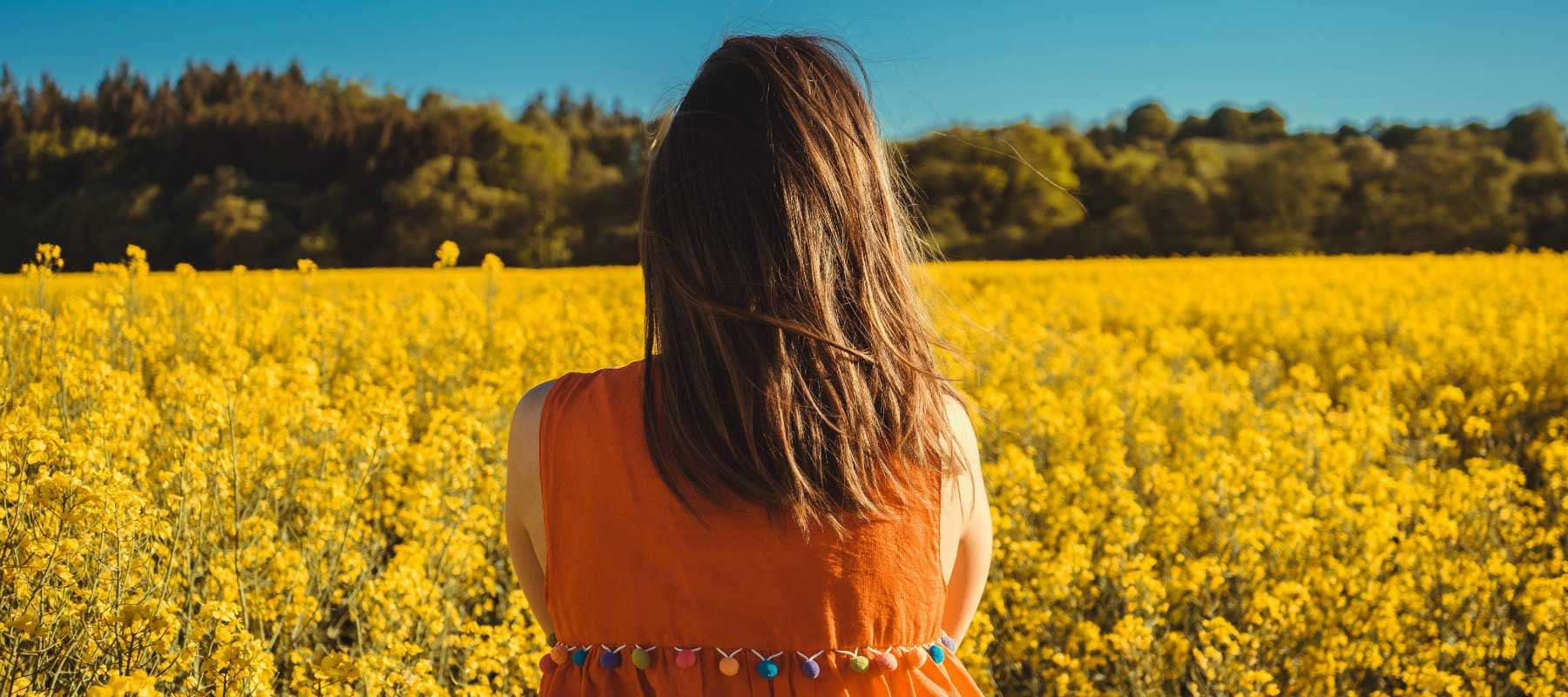 woman looking at field of flowers