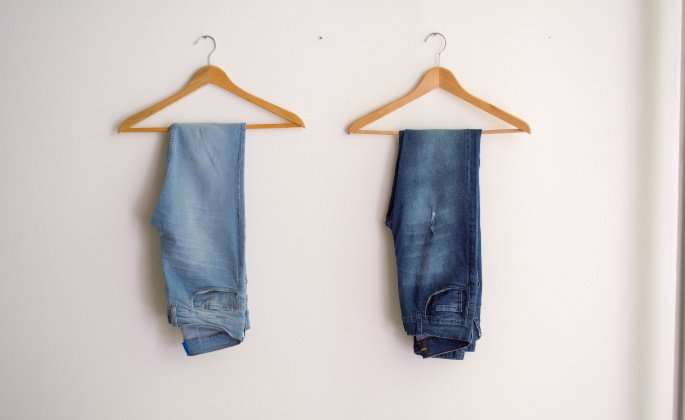 Two blue jeans on hangers
