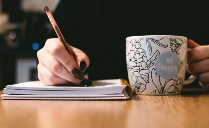 Girl with tea writing
