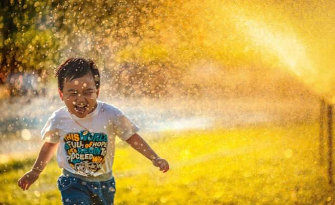 Kid running through sprinkler